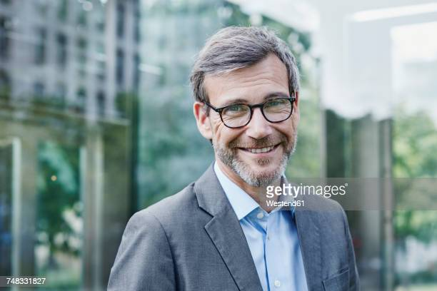portrait of smiling mature businessman outdoors - einzelner mann über 40 stock-fotos und bilder