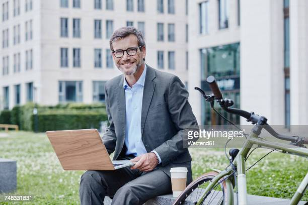 portrait of smiling mature businessman outdoors with laptop, takeaway coffee and bicycle - green suit stock pictures, royalty-free photos & images