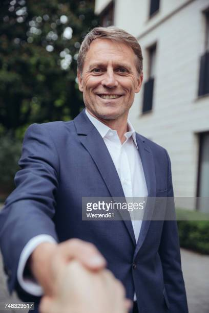 Portrait of smiling mature businessman shaking hands outdoors