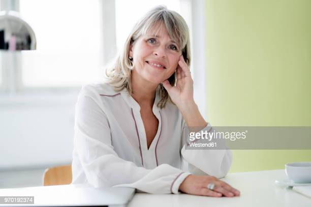Portrait of smiling mature businesswoman at desk