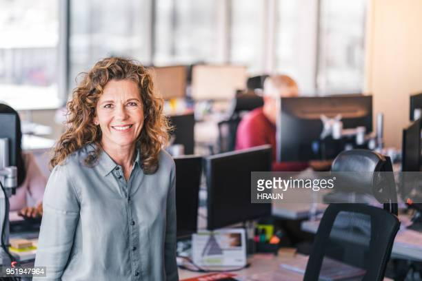 portrait of smiling mature businesswoman at office - 45 49 years stock pictures, royalty-free photos & images