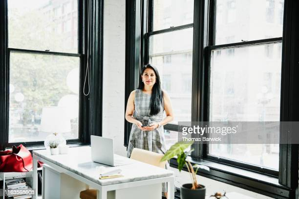 portrait of smiling mature businesswoman standing behind desk in creative office - independence stock pictures, royalty-free photos & images
