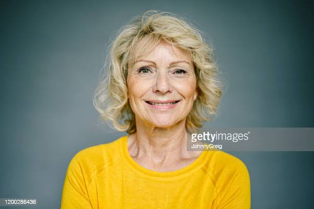 portrait of smiling mature caucasian woman in yellow top - mid length hair stock pictures, royalty-free photos & images