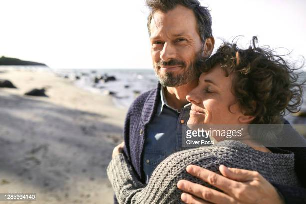 portrait of smiling mature couple embracing on the beach - 40 49 years stock pictures, royalty-free photos & images
