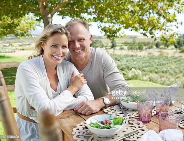 Portrait de souriant couple d'âge mûr sur table de petit déjeuner dans le jardin