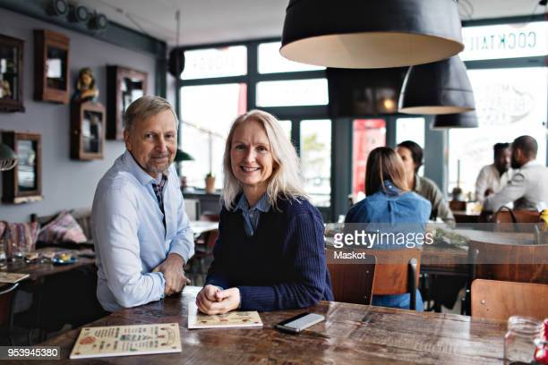 portrait of smiling mature couple with menu at wooden table against people in restaurant - 50 59 years stock pictures, royalty-free photos & images