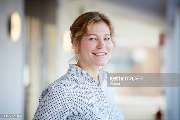 portrait of smiling mature entrepreneur standing at workplace - focus on foreground stock pictures, royalty-free photos & images