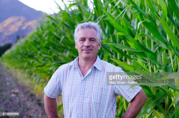 Portrait Of Smiling Mature Farmer Standing Against Plants