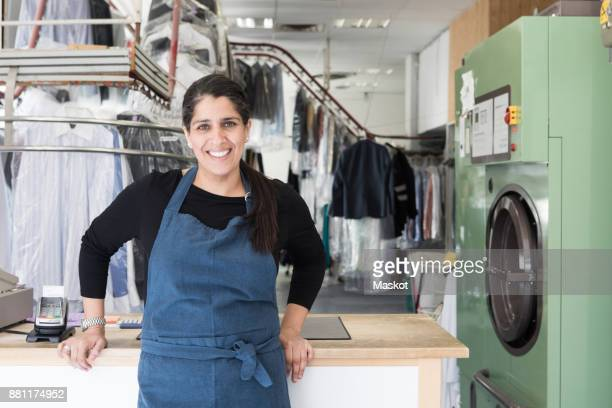 portrait of smiling mature female dry cleaner standing at laundromat - dry cleaner stock pictures, royalty-free photos & images