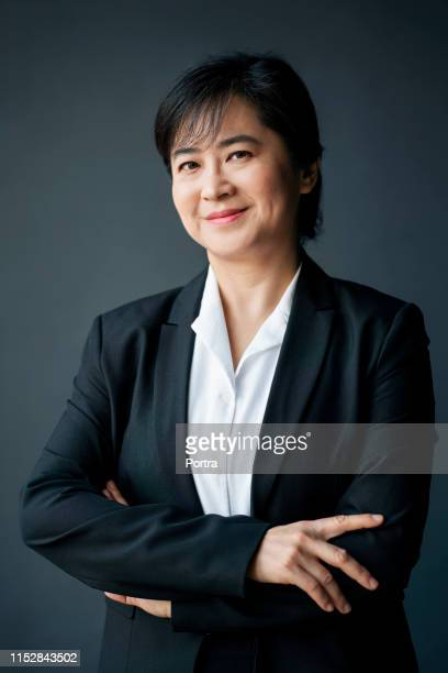 portrait of smiling mature female executive - coat stock pictures, royalty-free photos & images