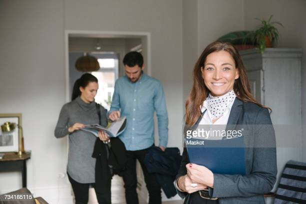 Portrait of smiling mature female realtor standing with couple discussing in background