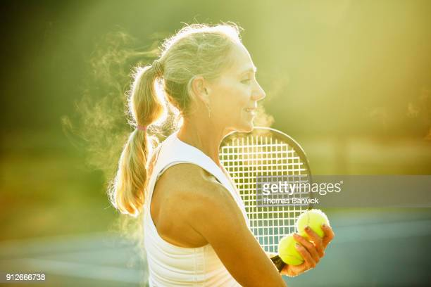 Portrait of smiling mature female tennis player during early morning tennis practice