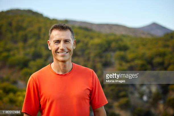 portrait of smiling mature man against mountain - mature men stock pictures, royalty-free photos & images