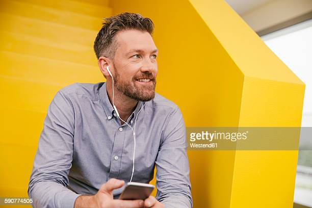 portrait of smiling mature man hearing music with smartphone and earphones sitting on yellow stairs - yellow photos et images de collection