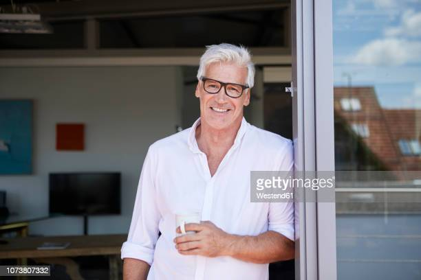 portrait of smiling mature man holding coffee cup at the balcony at home - lehnend stock-fotos und bilder