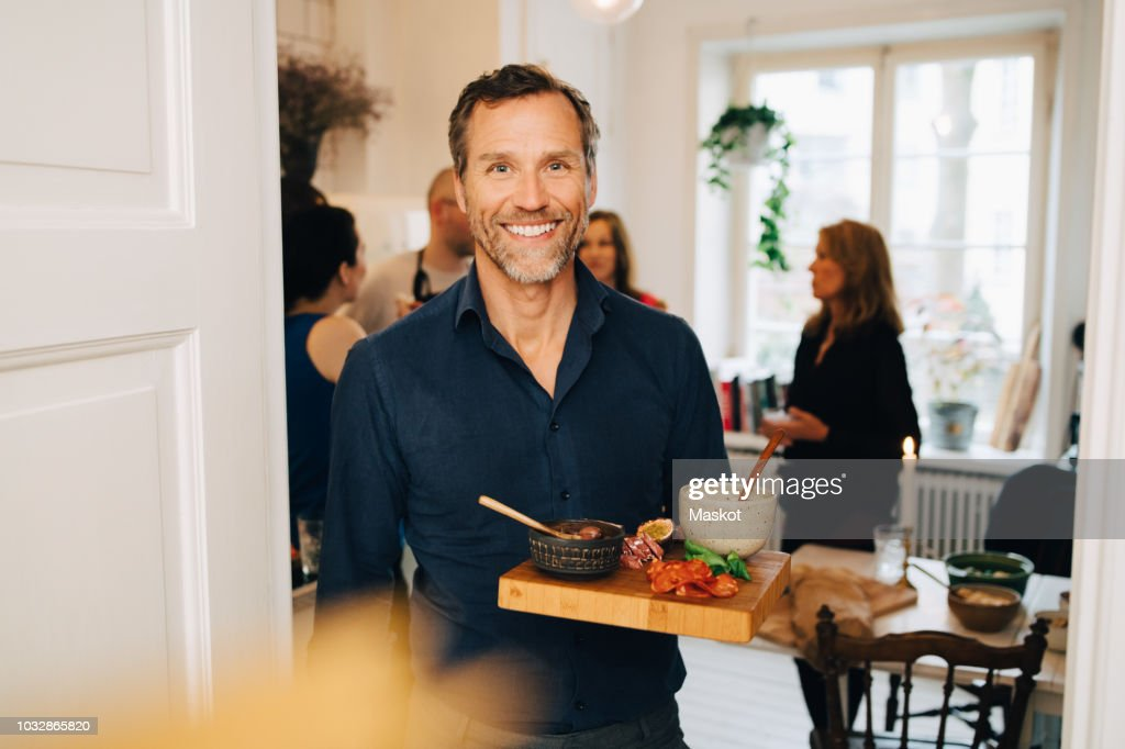 Portrait of smiling mature man holding food in serving tray while standing against friends at party : Foto de stock