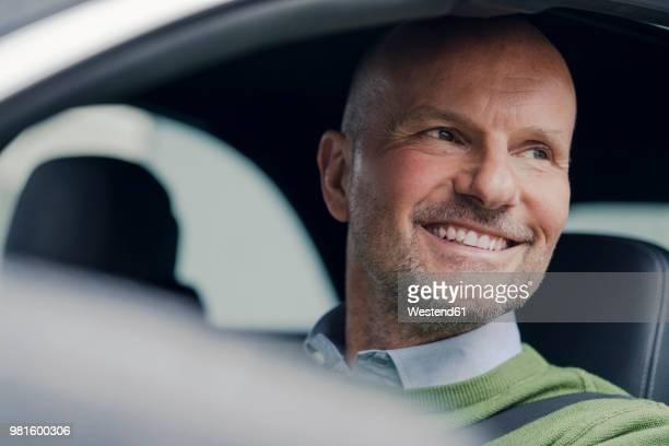 portrait of smiling mature man in car - steuern stock-fotos und bilder