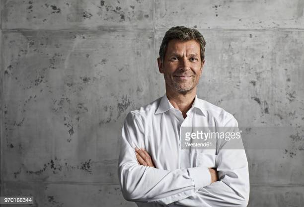 Portrait of smiling mature man in front of concrete wall