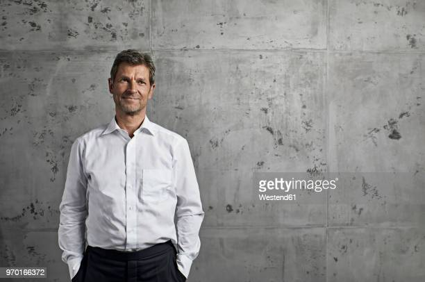 portrait of smiling mature man in front of concrete wall - overhemd stockfoto's en -beelden