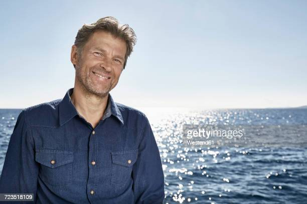 Portrait of smiling mature man in front of the sea