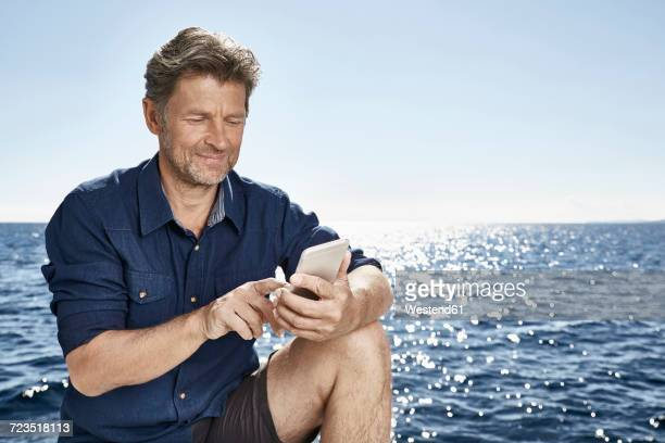 Portrait of smiling mature man in front of the sea using cell phone