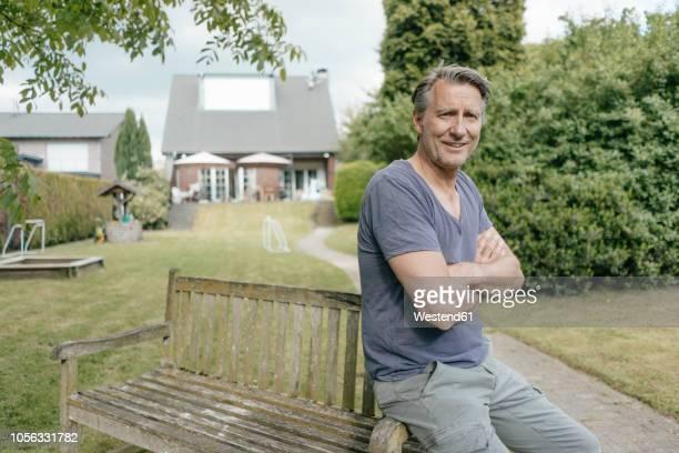 portrait of smiling mature man in garden of his home - stolz stock-fotos und bilder