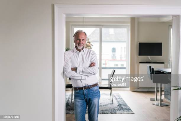 Portrait of smiling mature man leaning against door case in his apartment