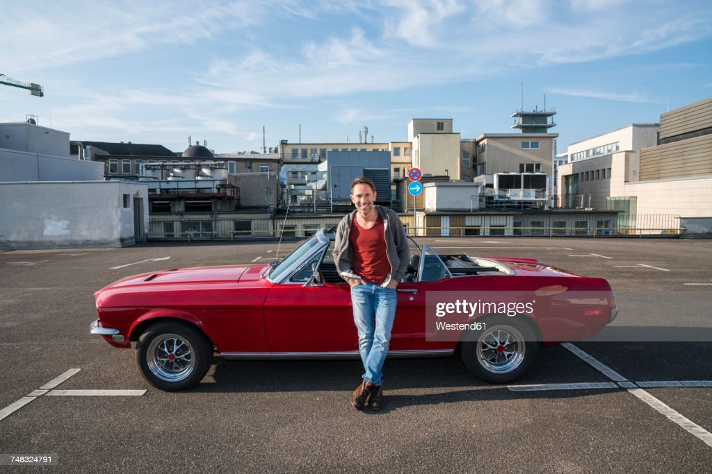 Portrait of smiling mature man leaning against his parked sports car : Stock Photo