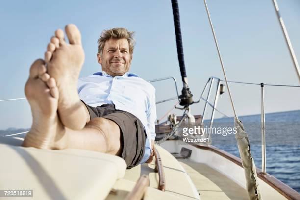 portrait of smiling mature man lying on deck of his sailing boat - male feet soles stock photos and pictures