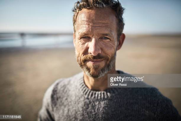 portrait of smiling mature man on the beach - selbstvertrauen stock-fotos und bilder