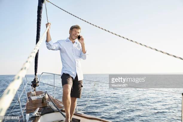 portrait of smiling mature man on the phone on his sailing boat - libre de droit photos et images de collection