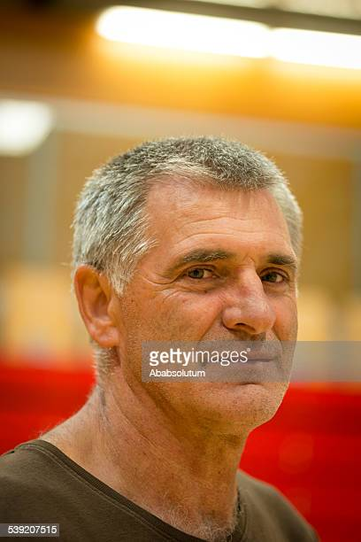 portrait of smiling mature man, school gymnasium, europe - hairy old man stock pictures, royalty-free photos & images