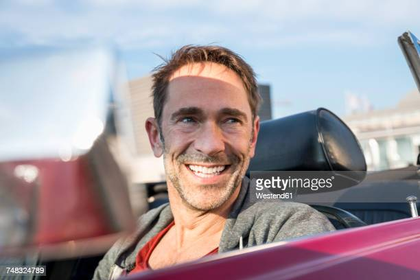 Portrait of smiling mature man sitting in his sports car