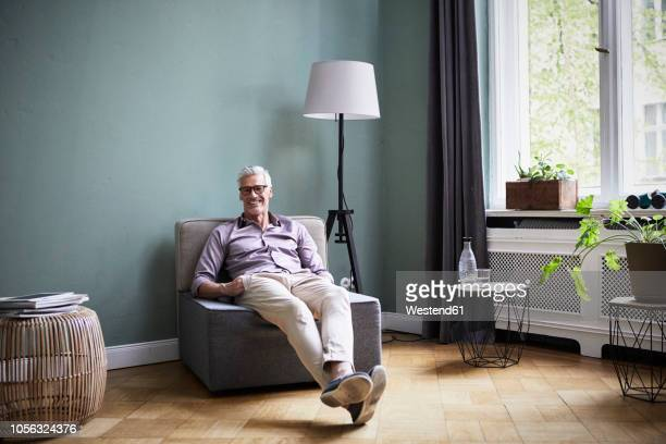 portrait of smiling mature man sitting on armchair at home - armstoel stockfoto's en -beelden