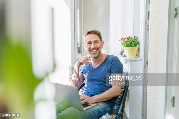 Portrait of smiling mature man sitting on balcony with laptop