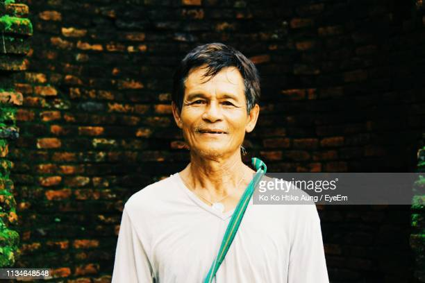 portrait of smiling mature man standing against brick wall - ko ko htike aung stock pictures, royalty-free photos & images