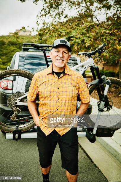 Portrait of smiling mature man standing at back of truck after mountain bike ride