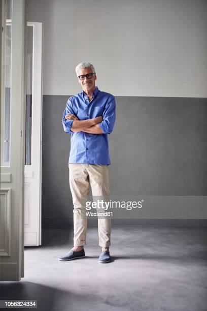 Portrait of smiling mature man standing beside open balcony door at home