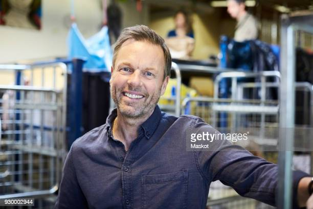 portrait of smiling mature man standing in illuminated warehouse - 55 59 jahre stock-fotos und bilder