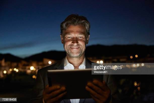 portrait of smiling mature man standing looking at tablet in the night - guardare verso il basso foto e immagini stock