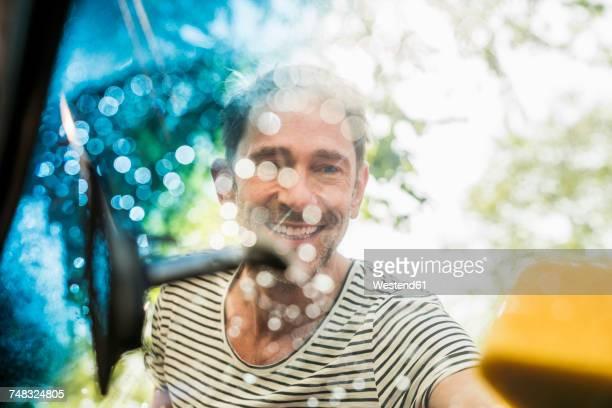 portrait of smiling mature man washing windscreen of his car - waschen stock-fotos und bilder