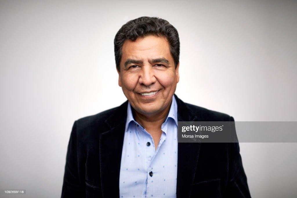 Portrait of smiling mature man wearing blazer : Stock Photo