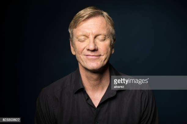 portrait of smiling mature man with closed eyes - eyes closed stock pictures, royalty-free photos & images