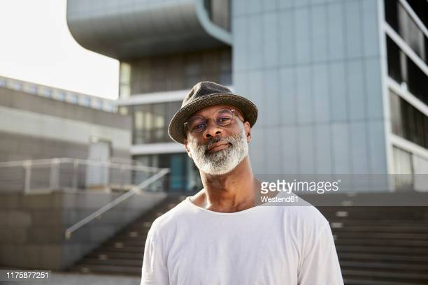 portrait of smiling mature man with grey beard wearing hat in summer - gray hat stock pictures, royalty-free photos & images