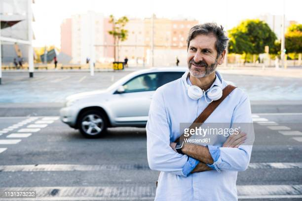 portrait of smiling mature man with headphones standing at a street - one mature man only stock photos and pictures