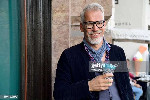 portrait of smiling mature man with reusable bamboo cup in the city - reusable stock pictures, royalty-free photos & images