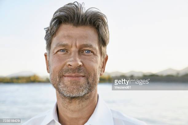 portrait of smiling mature man with stubble in front of the sea - handsome 50 year old men stock pictures, royalty-free photos & images