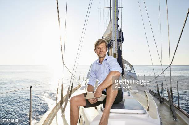 Portrait of smiling mature man with tablet sitting on his sailing boat