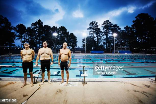 Portrait of smiling mature men standing on deck of outdoor pool before early morning workout