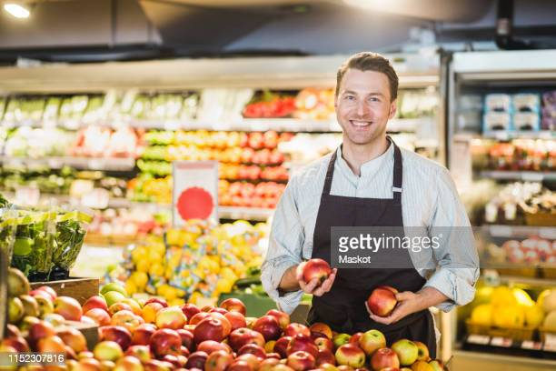 portrait of smiling mature owner standing at apple stall in grocery store - schürze stock-fotos und bilder